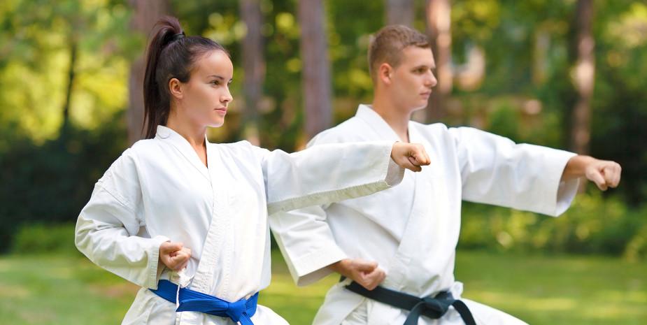 Young couple practicing karate doing Oi-tsuki punch.